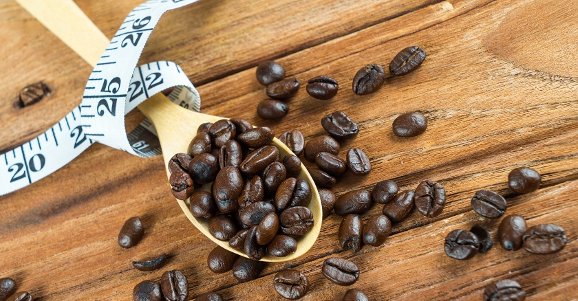 Coffee bean on wooden spoon and tape measure on wooden table background